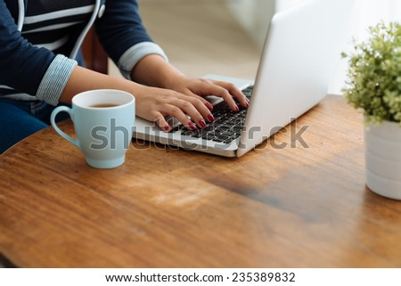 Cropped image of woman working on laptop at home - stock photo
