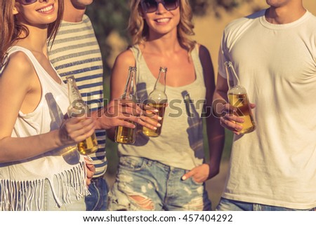 Cropped image of young beautiful people in casual clothes and sun glasses holding bottles of beverage, looking at camera and smiling while resting outdoors - stock photo