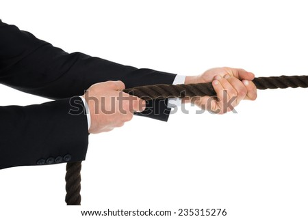 Cropped image of young businessman pulling rope over white background