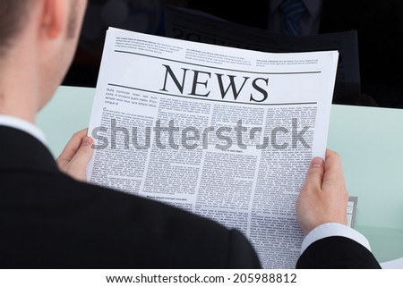 Cropped image of young businessman reading newspaper at office desk