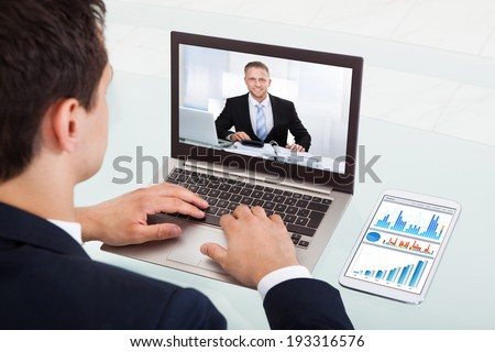 Cropped image of young businessman video conferencing on laptop at desk in office - stock photo