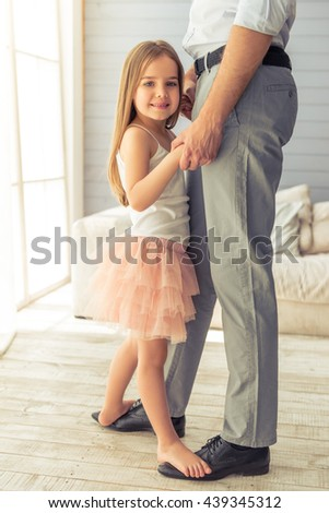 Cropped image of young father and his cute little daughter dancing at home. Girl is standing on her father's feet, looking at camera and smiling