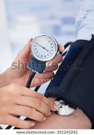 Cropped image of young female doctor checking blood pressure of businessman in clinic - stock photo