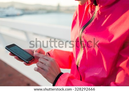 Cropped image of young female runner holding mobile phone with blank copy space screen while taking break between training, fit woman using cell telephone while resting after evening jog outdoors   - stock photo