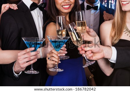 Cropped image of young friends toasting drinks at nightclub - stock photo