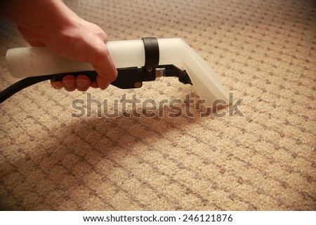 Cropped image of young maid cleaning carpet with vacuum cleaner at home - stock photo