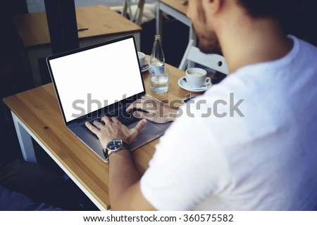 Cropped image of young man chatting via net-book during work break in coffee shop, male sitting in front open laptop computer with blank copy space screen for your text message or advertising content - stock photo