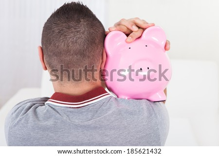 Cropped image of young man holding piggy bank at home