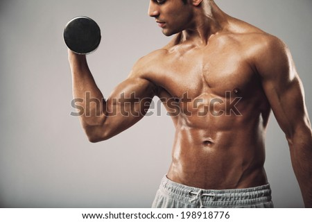 Cropped image of young muscular man doing heavy dumbbell exercise for biceps. Man working out with dumbbells on grey background. Fitness and workout concept. - stock photo