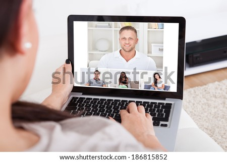 Cropped image of young woman using laptop for video conference at home - stock photo