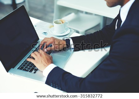 Cropped image view of man's hands keyboarding on net-book with blank copy space screen for your advertising content or text message,wealthy man working on a laptop computer during coffee break in cafe - stock photo