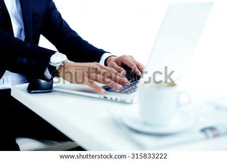 Cropped image view of man's hands with luxury wear watches keyboarding on net-book during coffee breaks, elegant successful male person working remotely on laptop computer at breakfast in a restaurant - stock photo