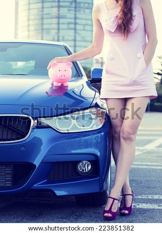 Cropped image woman customer, agent standing next to new car, piggy bank on hood isolated outside outdoor. Dealership offering credit line finance services. Lease automobile purchase financing concept - stock photo