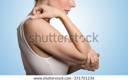 Cropped image woman with joint inflammation. Female's elbow. Arm pain and injury concept. Closeup side profile woman with painful elbow isolated on blue background - stock photo