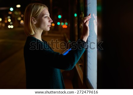Cropped image young woman touching big digital display while standing in night city with reflected on her screen light, attractive female doing internet money payment with automated teller machine - stock photo