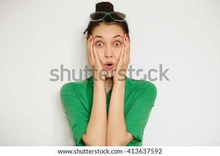 Cropped isolated portrait of beautiful astonished woman looking at the camera, surprised with big sale prices. Headshot of brunette female holding her face shock after receiving some sensational news - stock photo