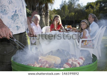 Cropped man grilling with family sitting at table in the background - stock photo
