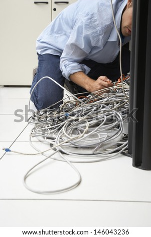 Cropped man working on tangled computer wires in office