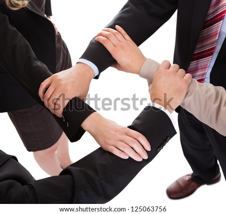 Cropped overhead view of a diverse group of businesspeople linking hands in a team - stock photo