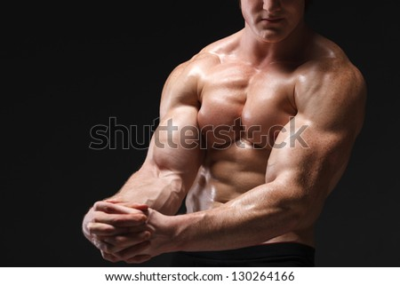 Cropped picture of muscle man posing in studio over dark background - stock photo