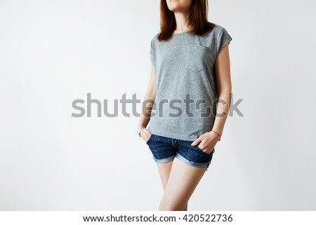 Cropped portrait of attractive young brunette female model posing in gray blank copy space T-shirt for your promotional content standing against white studio wall. Advertising and design concept - stock photo