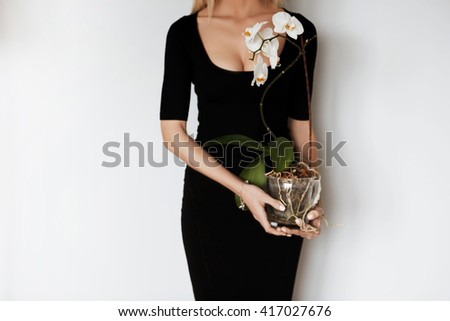 Cropped portrait of beautiful slim woman wearing elegant black midi dress with low neck, holding orchid pot while posing against white studio wall. Young female taking care after flowers at home - stock photo