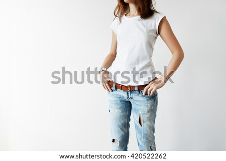 Cropped portrait of beautiful teenage girl with dark hair posing against white studio wall wearing stylish blue ripped jeans and white blank T-shirt with copy space for your advertising content  - stock photo