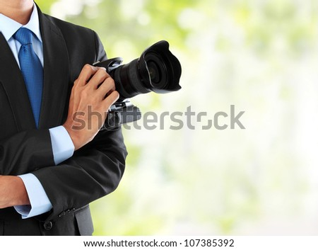 cropped portrait of professional photographer holding dslr camera with copy space - stock photo