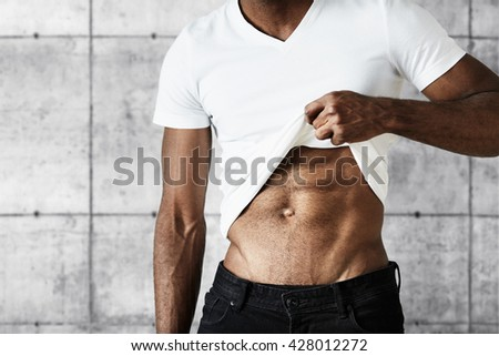 Cropped portrait of young black athletic man wearing black jeans and white T-shirt showing off his muscles Attractive African male demonstrating his fit muscular body posing against gray concrete wall - stock photo