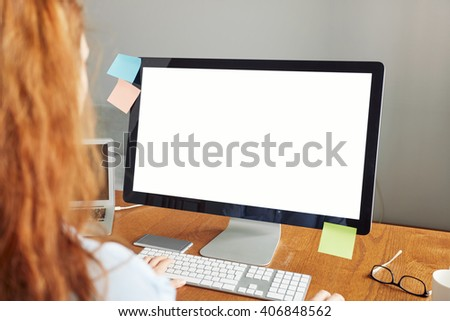 Cropped rear portrait of young student with red hair wearing blue shirt typing on PC keyboard while sitting at the desk, keyboarding text of course work, using laptop with white blank copy space - stock photo