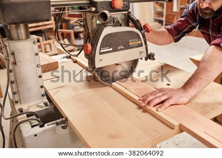 Cropped shot of a carpenter using a radial arm circular saw to cut a plank of wood, in his woodwork studio - stock photo