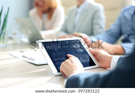 Cropped shot of a group of businesspeople looking at graphs on digital tablets