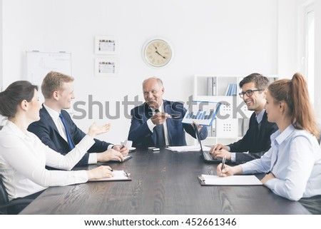Cropped shot of a happy group of business people  in the middle of discussion, sitting at the table - stock photo