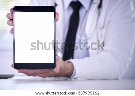 Cropped shot of a male doctor using a digital tablet.He is showing digital tablet with blank screen to the camera. - stock photo