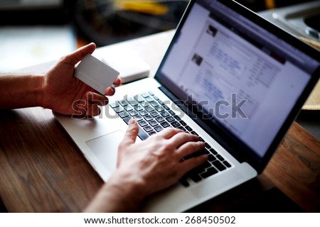 Cropped shot of a man's hands using a laptop at home while holding credit card in the hands, on-line shopping at home, cross process, filtered image - stock photo