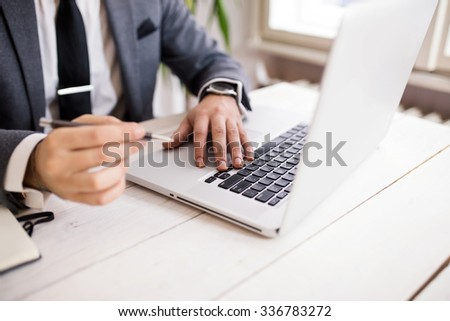 Cropped shot of a young businessman working from office using notebook computer, man's hands, man at his workplace using technology, taking notes in his notebook, depth of field, selective focus - stock photo