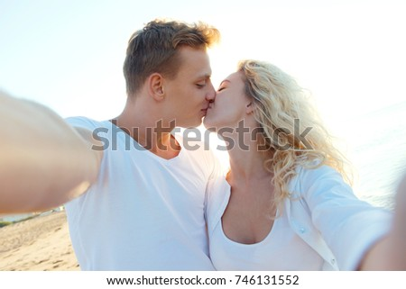 Cropped shot of a young kissing couple taking a selfie on the beach
