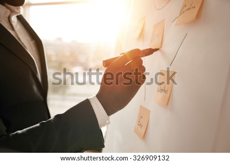 Cropped shot of businessman putting his ideas on white board during a presentation in conference room. Focus in hands with marker pen writing in flipchart. - stock photo
