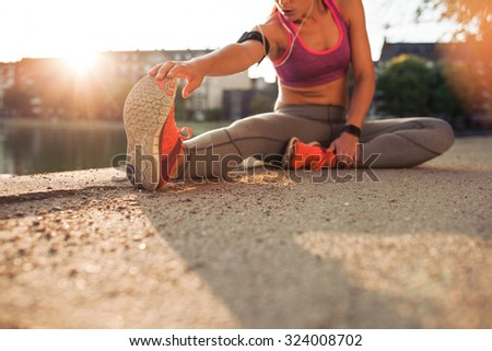 Cropped shot of female runner stretching legs before doing her summer workout. Woman warming up before outdoor workout with sun flare. - stock photo