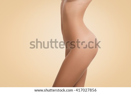 Cropped shot of female with perfect slim body and tanned skin posing naked against blank copy space wall for your promotional content. Young woman having spa procedures. Beauty and cosmetology concept - stock photo
