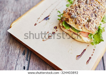 Cropped shot of fresh roll with whole grain seeds on top, filled with fresh sandwich ingredients and presented on brown paper on a wooden board - stock photo