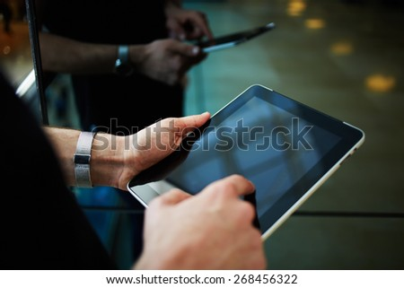 Cropped shot of male person using a digital tablet, man's hand typing text message zooming digital image on touchpad, businessman using his wireless devices during a meeting, work on a tablet screen - stock photo