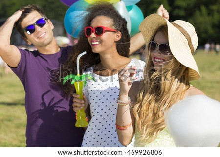 Cropped shot of smiling friends at a music festival, ethnic girl holding a drink