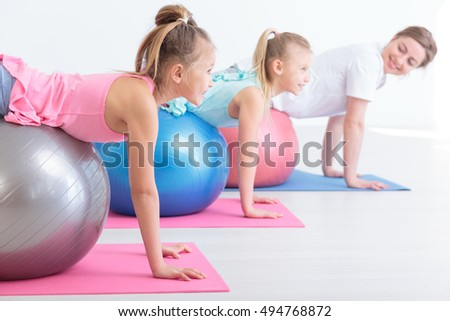 Cropped shot of two little girls and their physiotherapist during streching exercises