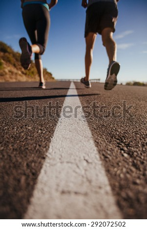 Cropped shot of two people running on road. Athletes training on country road. Low angle shot with focus on road. - stock photo