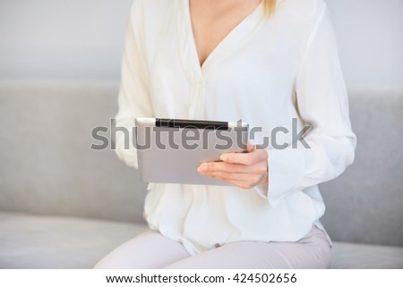 Cropped shot of woman using digital tablet, sitting on the sofa. Female entrepreneur checking email and reading news on electronic device in the morning before going to the office.  Selective foucs - stock photo