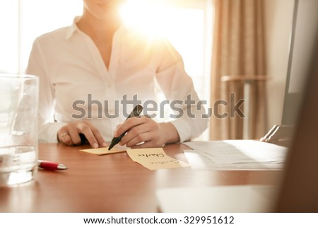 Cropped shot of woman writing some names on sticky notes while sitting in conference room. - stock photo