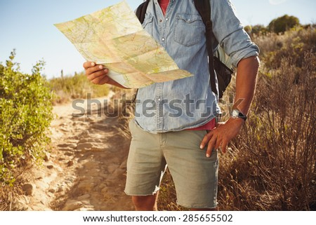 Cropped shot of young man hiking in countryside reading a map for directions. - stock photo