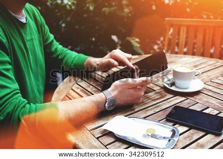 Cropped shot view of a man's hand keyboarding on touch pad while sitting in sidewalk cafe in summer day, male freelancer using digital tablet for remote work during breakfast time in sidewalk cafe  - stock photo