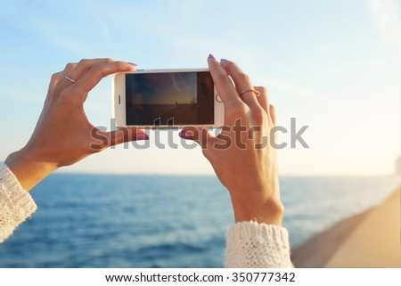 Cropped shot view of a woman's hands making photo with mobile phone digital camera for for social network picture, female tourist photographing amazing sea view on cell telephone during summer trip  - stock photo